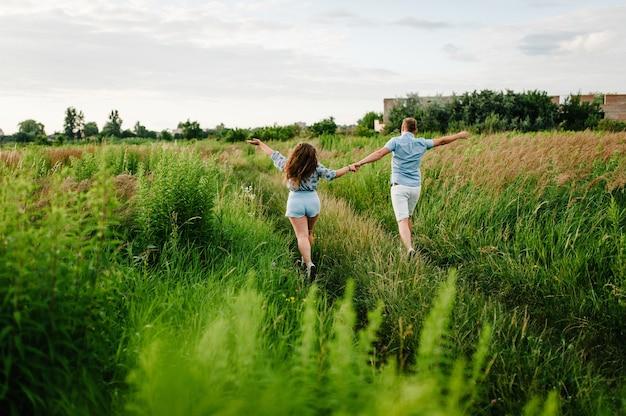 Vista traseira de um homem romântico e uma mulher caminhando na grama do campo, a natureza apreciando o pôr do sol deslumbrante. conceito de linda família de mãos dadas. jovem casal correndo e olhando para longe.