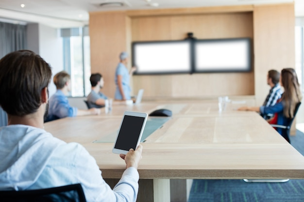 Vista traseira de um homem segurando um tablet enquanto participa de uma reunião na sala de conferências
