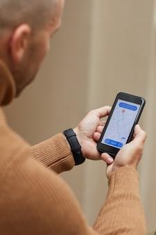 Vista traseira de um homem segurando um telefone celular e seguindo em direção ao carro no mapa, ele esperando o táxi
