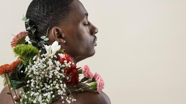 Vista traseira de um homem sem camisa posando com um buquê de flores e copie o espaço