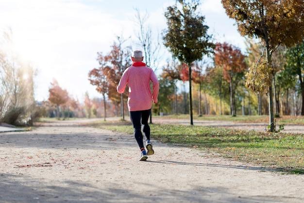 Vista traseira de um homem sênior com roupas esportivas correndo no parque em um dia ensolarado