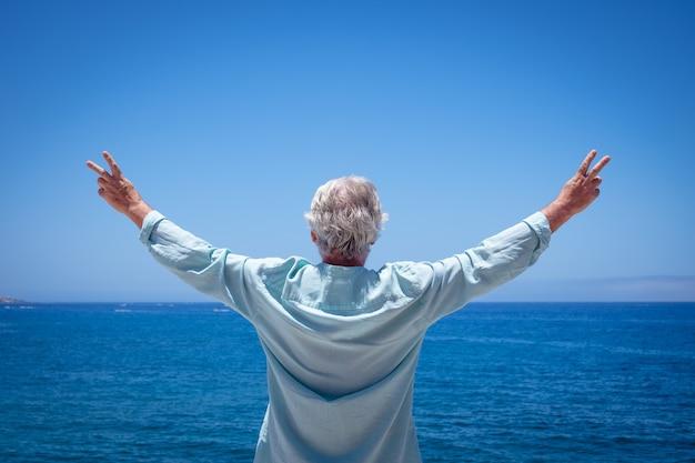 Vista traseira de um homem sênior curtindo as férias no mar, olhando para o horizonte sobre a água com os braços estendidos