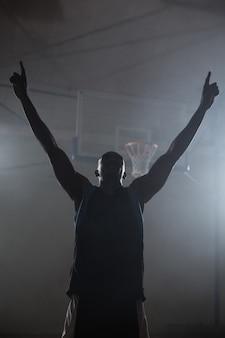 Vista traseira de um jogador de basquete com os braços no ar