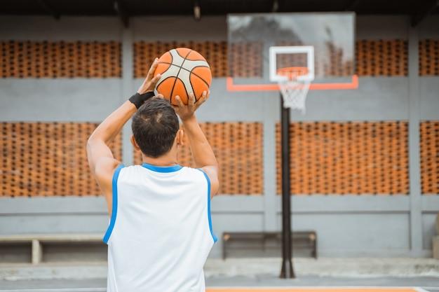 Vista traseira de um jogador de basquete segurando a bola enquanto arremessa no aro