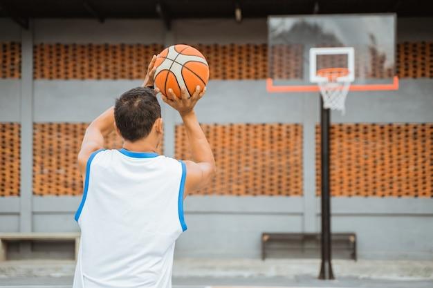 Vista traseira de um jogador de basquete segurando a bola enquanto arremessa para o aro