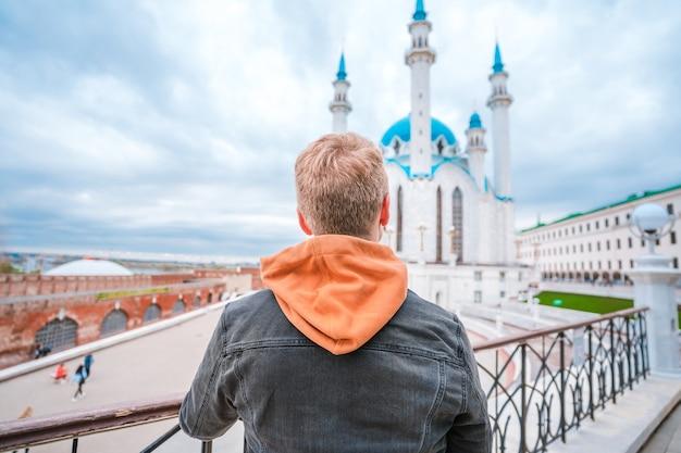 Vista traseira de um jovem admirando uma mesquita em kazan, rússia