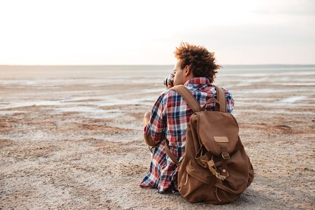 Vista traseira de um jovem africano com uma mochila sentado e tirando fotos na praia