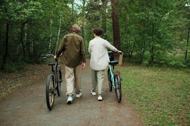 Vista traseira de um jovem casal em trajes casuais conversando enquanto desce o caminho da floresta ou estrada entre árvores verdes