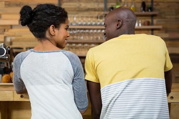 Vista traseira de um jovem casal olhando um para o outro em uma cafeteria