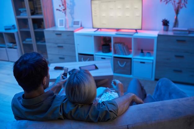 Vista traseira de um jovem casal se abraçando enquanto está sentado no sofá, comendo pipoca e assistindo a um filme