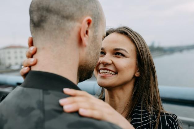 Vista traseira de um jovem casal sentado ao lado de um lago tocando suas cabeças apaixonadas. casal apaixonado em um encontro sentado ao ar livre perto de um lago com um copo de vinho.