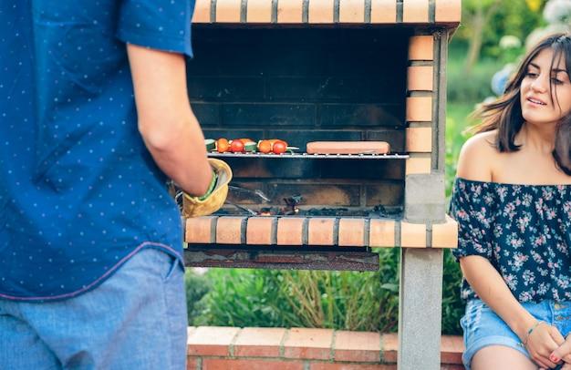 Vista traseira de um jovem cozinhando salsichas e espetos de vegetais em uma churrasqueira de tijolos, enquanto uma mulher está olhando para uma festa de verão ao ar livre