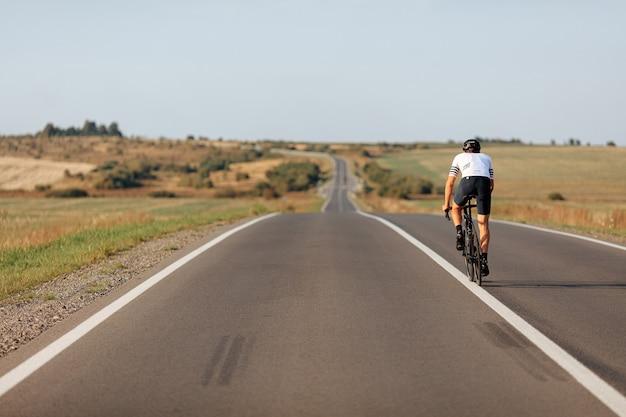 Vista traseira de um jovem desportivo pedalando na linha de separação branca da estrada