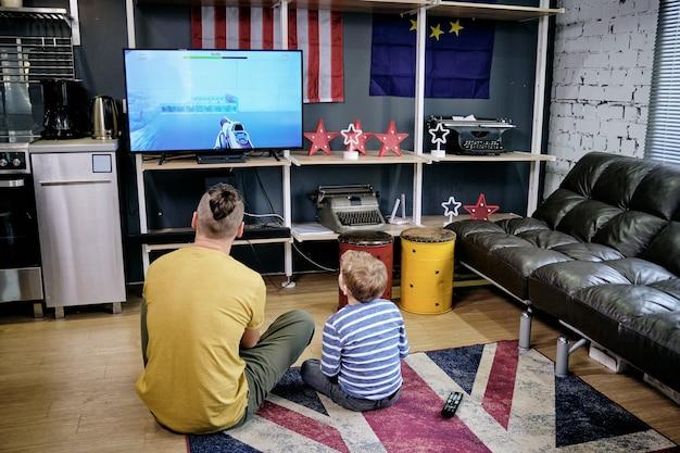 Vista traseira de um jovem e um garotinho jogando videogame no chão em casa