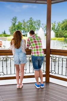 Vista traseira de um jovem e uma mulher encostados na grade do gazebo de madeira em frente a uma cachoeira artificial em um parque com lago, fonte e árvores diferentes