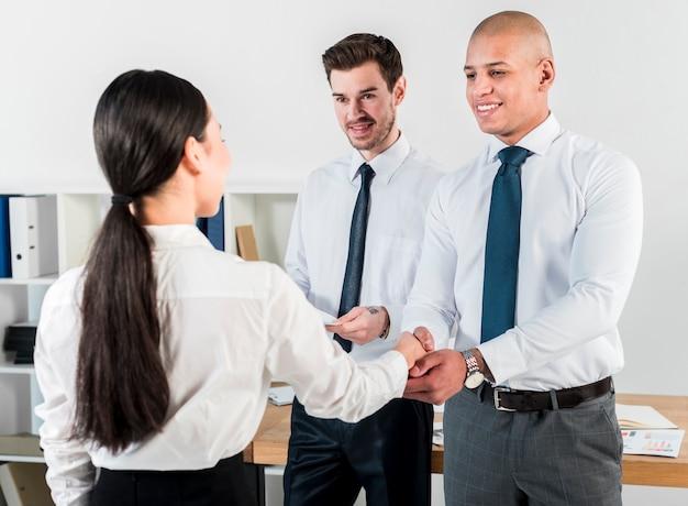Vista traseira, de, um, jovem, executiva, apertar mão, com, homem negócios