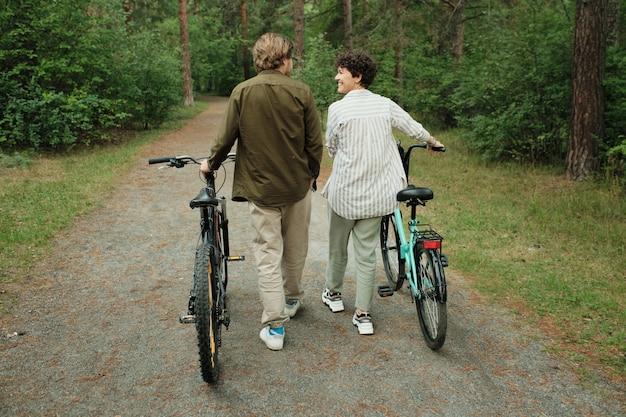 Vista traseira de um jovem marido e mulher felizes em trajes casuais conversando enquanto se movem pelo caminho da floresta ou pela estrada, depois de andar de bicicleta