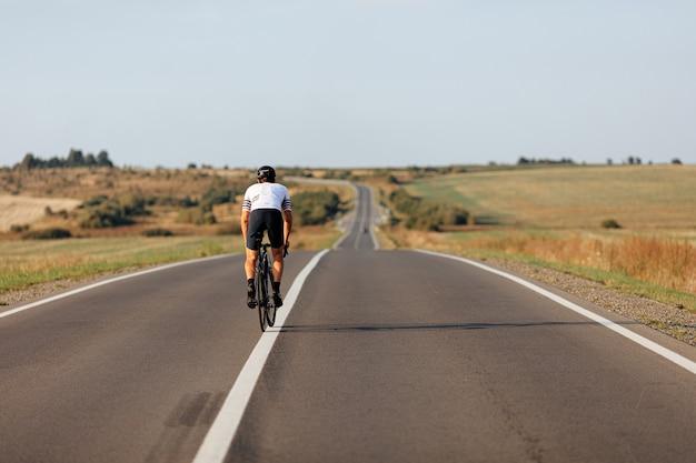 Vista traseira de um jovem musculoso em roupa esportiva e capacete protetor em uma bicicleta ao longo do campo