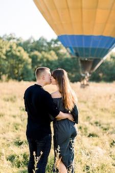 Vista traseira de um lindo casal romântico em roupas pretas elegantes, abraçando-se, em pé no campo ensolarado de verão com balão de ar quente