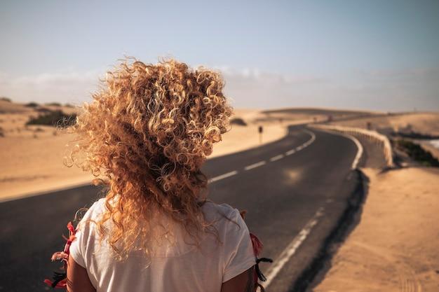 Vista traseira de um longo cabelo loiro encaracolado ao vento para o conceito de férias de independência de liberdade