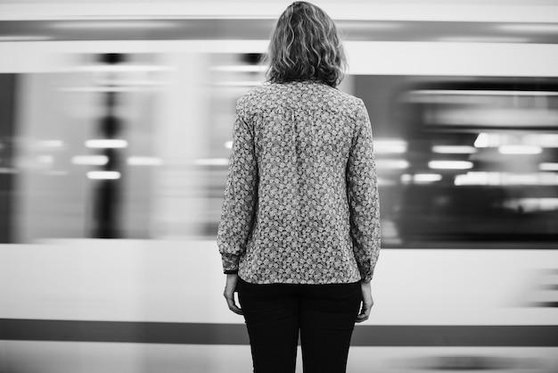 Vista traseira, de, um, loura, mulher espera, em, a, trem, plataforma