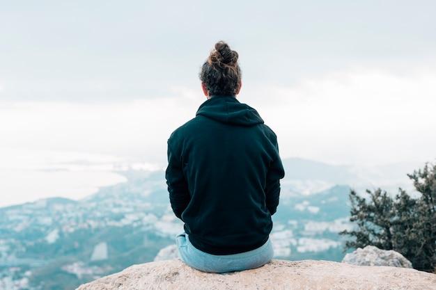 Vista traseira, de, um, macho, hiker, sentando, cima, um, montanha, desfrutando, vista cidade