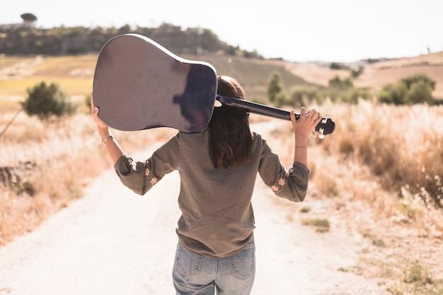 Vista traseira, de, um, menina adolescente, com, guitarra, ficar, ligado, estrada sujeira