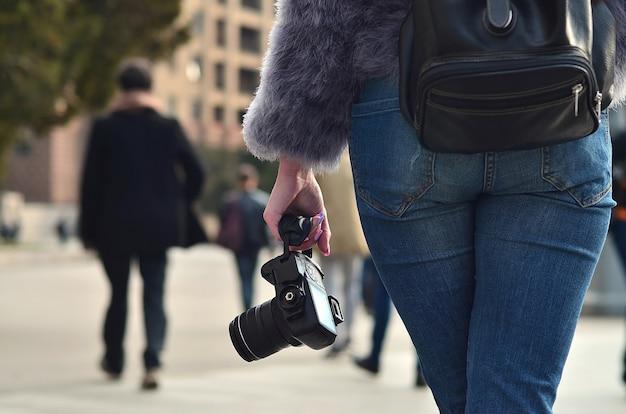 Vista traseira, de, um, menina, com, um, câmera digital, ligado, um, aglomerado, rua