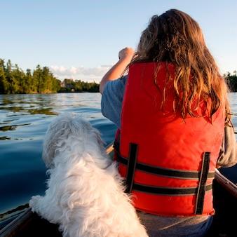 Vista traseira, de, um, menina, sentando, ligado, bote, com, um, cão, lago, de, a, madeiras, ontário, canadá