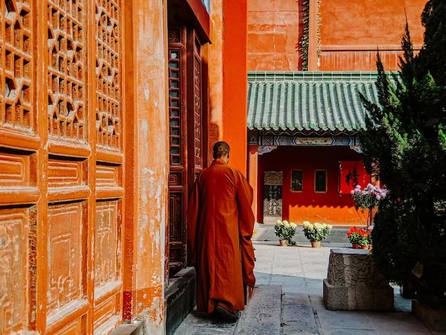 Vista traseira de um monge em um uniforme laranja caminhando perto de
