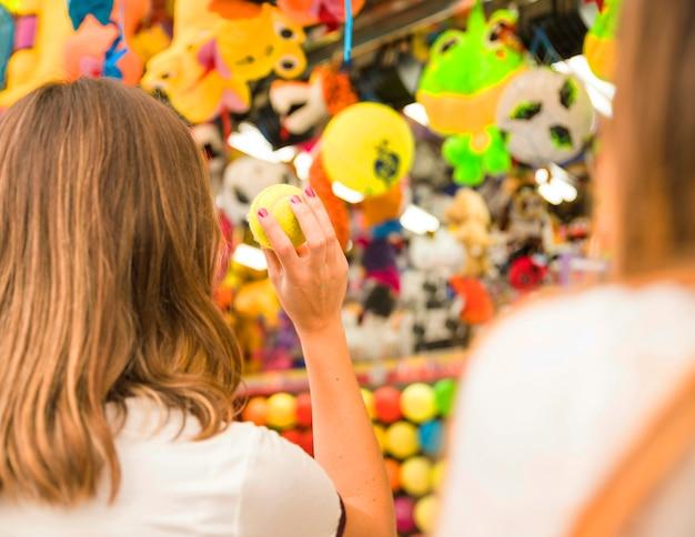 Vista traseira, de, um, mulher, visando, brinquedos, com, bola tênis