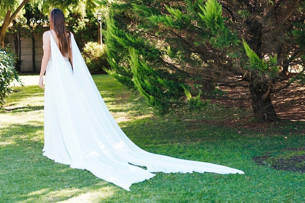 Vista traseira, de, um, noiva, em, branca, longo, vestido, andar, parque