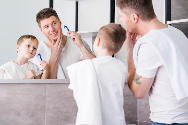 Vista traseira, de, um, pai filho, olhando espelho, segurando, navalha, em, mão