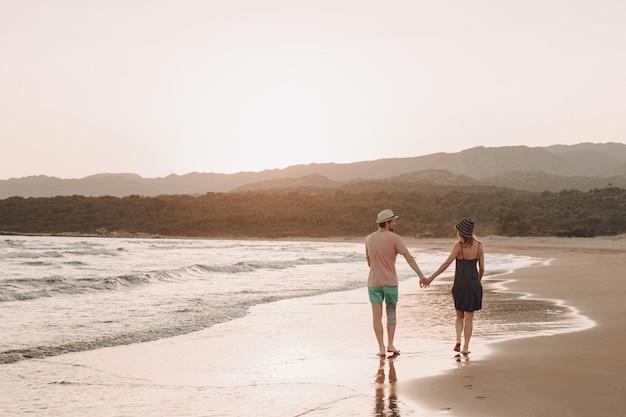 Vista traseira, de, um, par hipster romântico, andar, em, praia, durante, verão, férias, em, pôr do sol