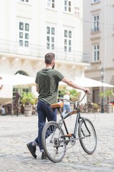 Vista traseira, de, um, posição homem, com, seu, bicicleta, ligado, rua cidade