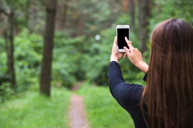 Vista traseira, de, um, posição mulher, em, a, floresta, tocar, a, cellphone, tela