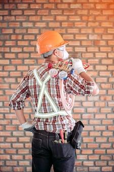 Vista traseira de um técnico especialista em ar condicionado em uniforme de segurança padrão