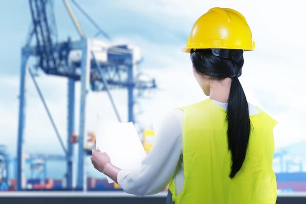 Vista traseira de um trabalhador da construção civil asiático com capacete de segurança segurando o papel de planejamento