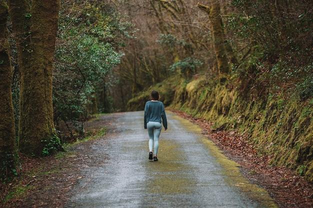 Vista traseira de uma atleta irreconhecível em roupas esportivas, caminhando ao longo da estrada de asfalto na floresta durante o treinamento cardiovascular