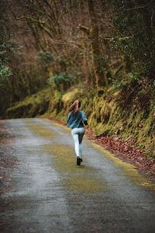 Vista traseira de uma atleta irreconhecível em roupas esportivas, correndo ao longo da estrada de asfalto na floresta durante o treinamento cardiovascular