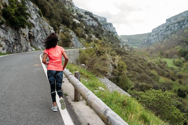 Vista traseira de uma atleta negra em activewear correndo em rota pavimentada com cerca contra vale de montanha de paisagem