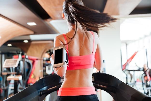 Vista traseira de uma bela jovem atleta com tela balnk em um smartphone correndo na esteira na academia