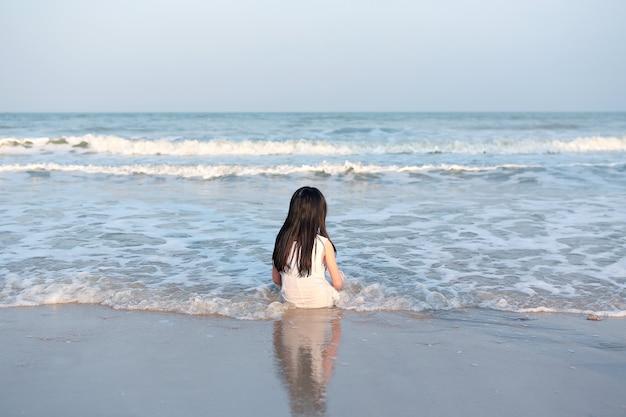 Vista traseira de uma criança asiática sentada na praia de areia