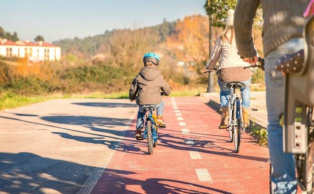 Vista traseira de uma família feliz com crianças andando de bicicleta perto da natureza em um dia ensolarado de inverno