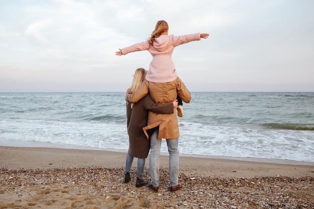 Vista traseira de uma família sorridente com uma filha pequena