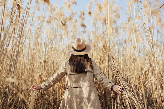 Vista traseira de uma garota andando em juncos secos