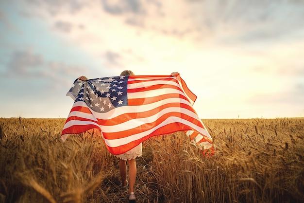 Vista traseira de uma garota de vestido branco usando uma bandeira americana em um campo de trigo