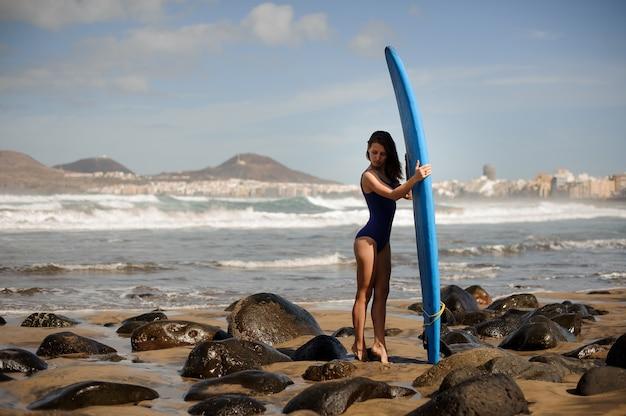 Vista traseira de uma garota esportiva de maiô azul em pé com a prancha de surfe sobre o oceano atlântico
