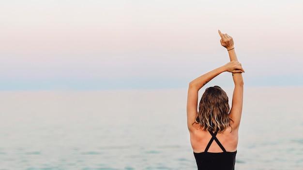 Vista traseira de uma garota esticando os braços para cima na praia