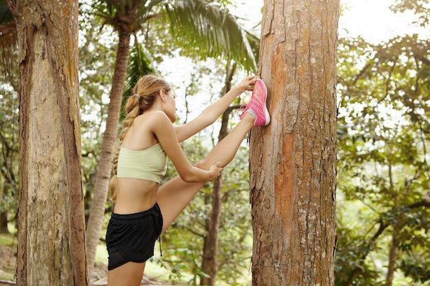 Vista traseira de uma garota loira esportiva com sutiã esportivo verde e shorts pretos, esticando os músculos, esticando a perna contra a árvore, preparando-se para um treino de corrida.